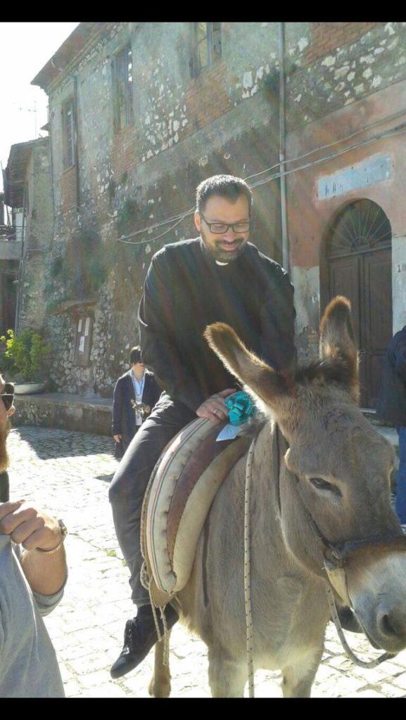 Don Christian Medos su un mulo per il centro storico di Artena